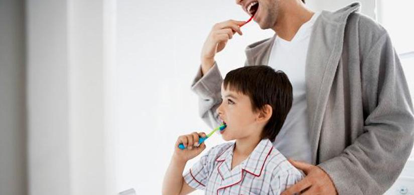 Pai e filho a escovar os dentes