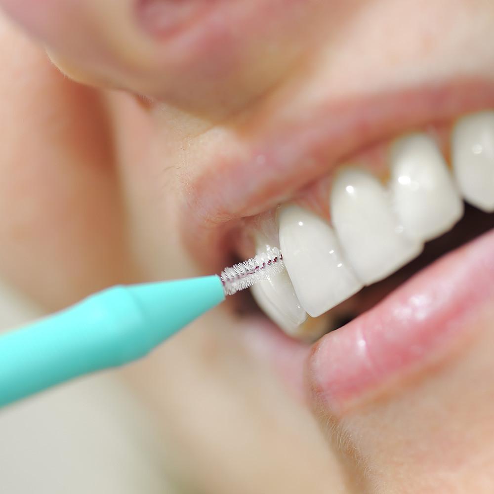 Pessoa sorrindo usando escova interdental