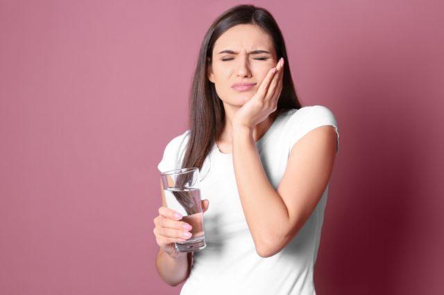 Mulher com dentes sensíveis segurando copo de água