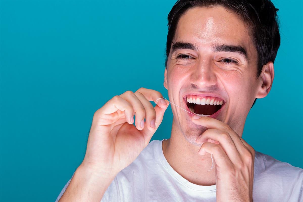 Homem sorrindo passando fio dental