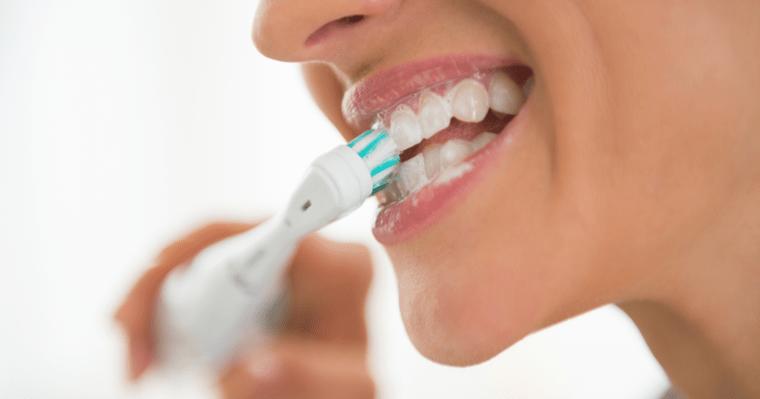 Mulher escovando os dentes com escova elétrica